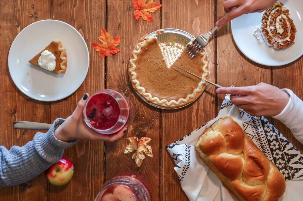 A wooden table set for Thanksgiving with decorative leaves and Pumpkin Pie