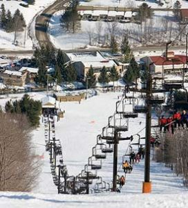 A chairlift brings skiers and snowboarders up a snowy mountain.