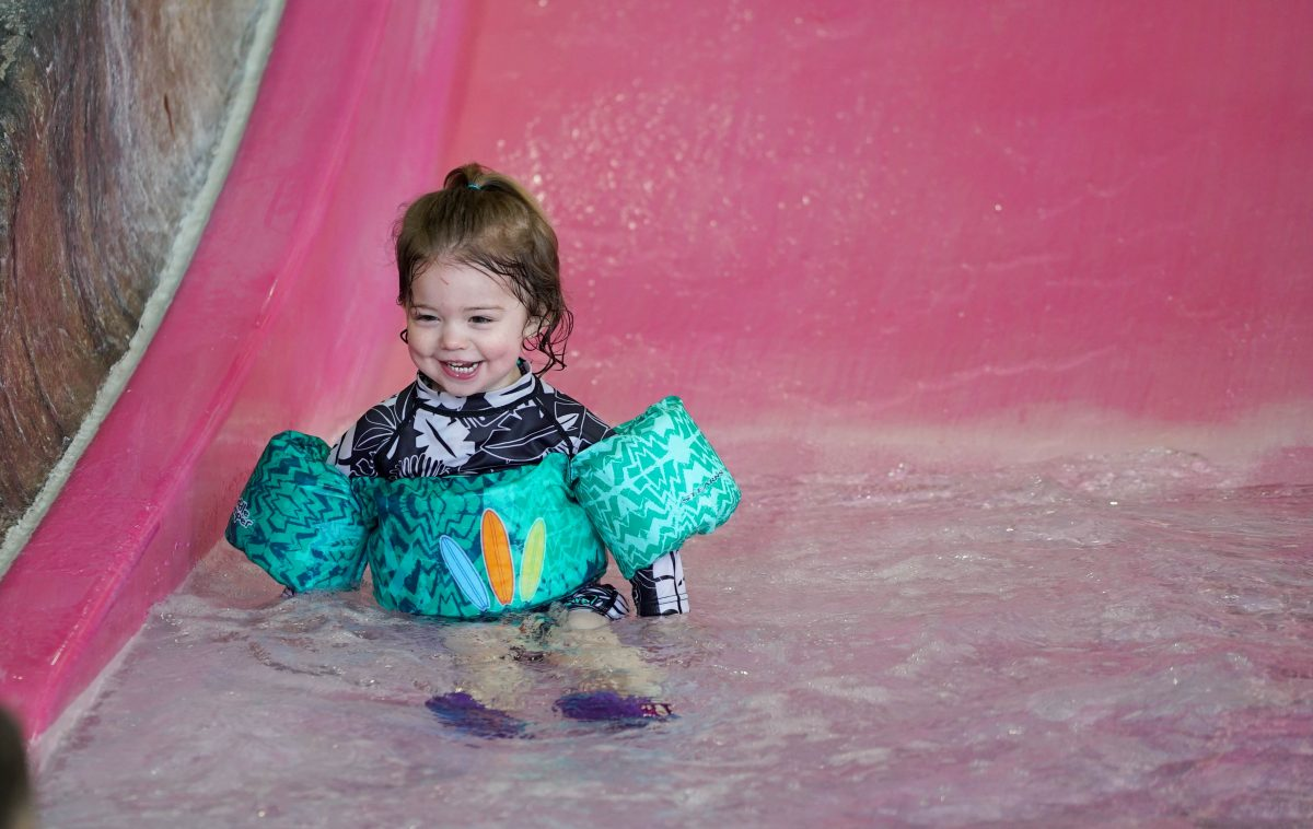 Child sliding down a small waterslide into a shallow pool