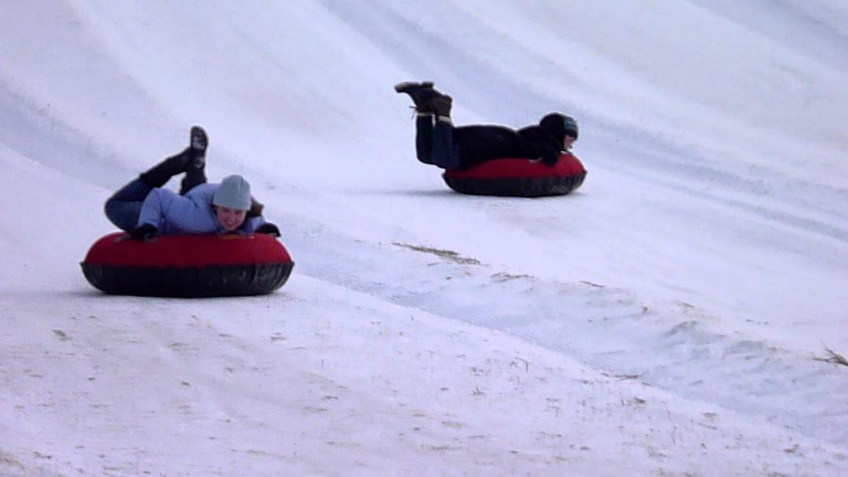 2 people ride down the hill on red tubes