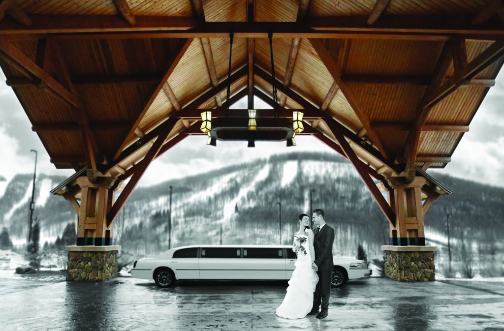 Bride and groom standing under car port of Hope Lake Lodge in front of a limo with the mountain in the background.