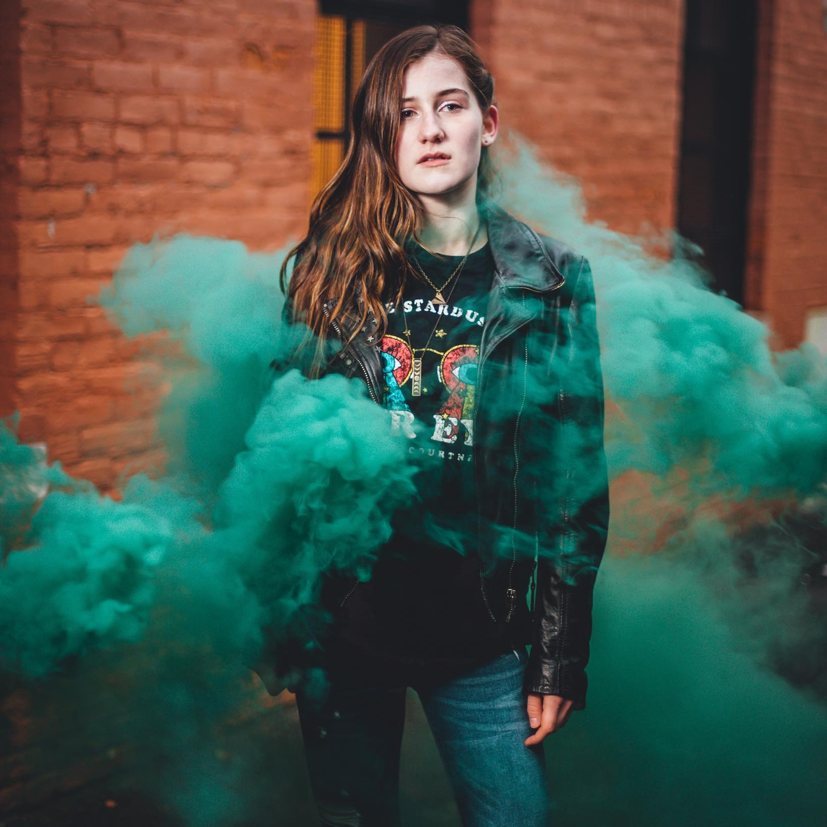Photo of singer-songwriter Sydney Irving in a haze of emerald green smoke in front of an orange brick building