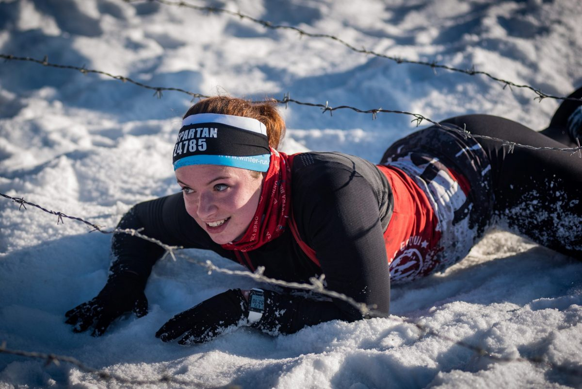 2020 Spartan at Greek Peak - racer crawling under barbed wire in the snow.