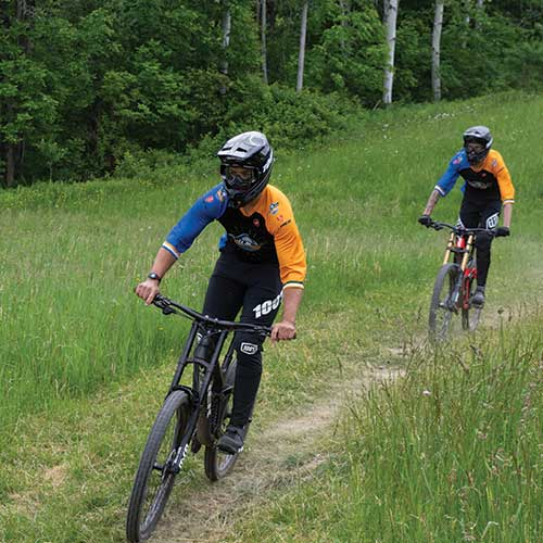 Two people Mountain Biking at Greek Peak on some wooded trails