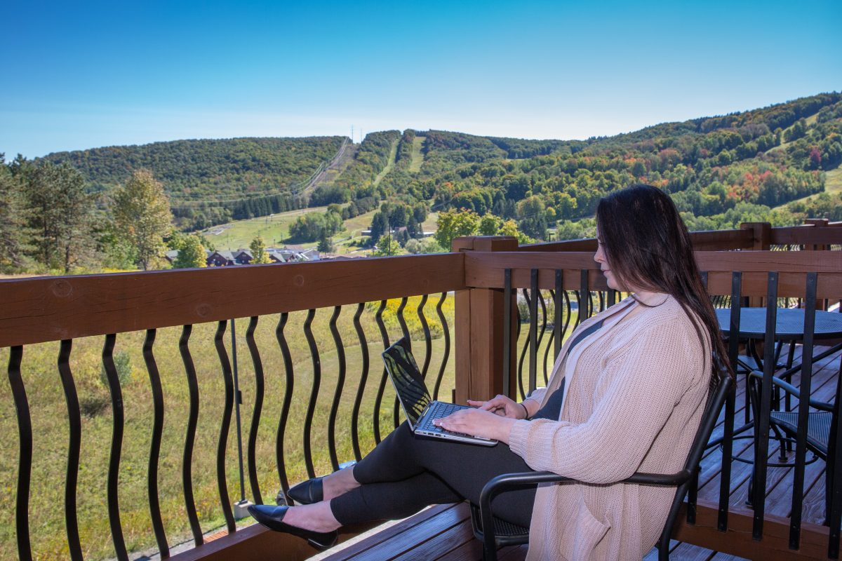 Woman sitting with Laptop overlooking balcony with Mountains in the background