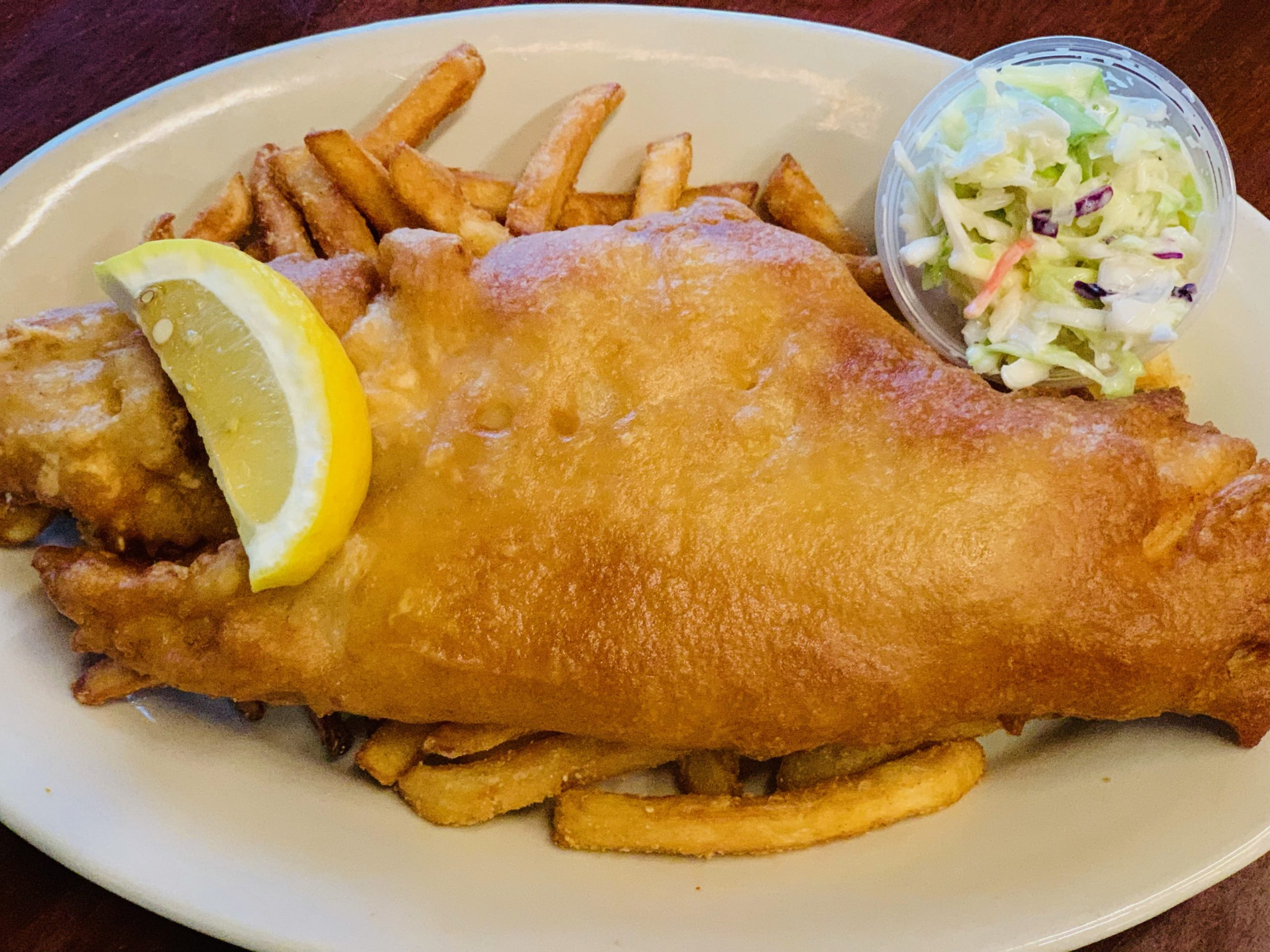 plate of fried fish with french fries and a lemon and coleslaw