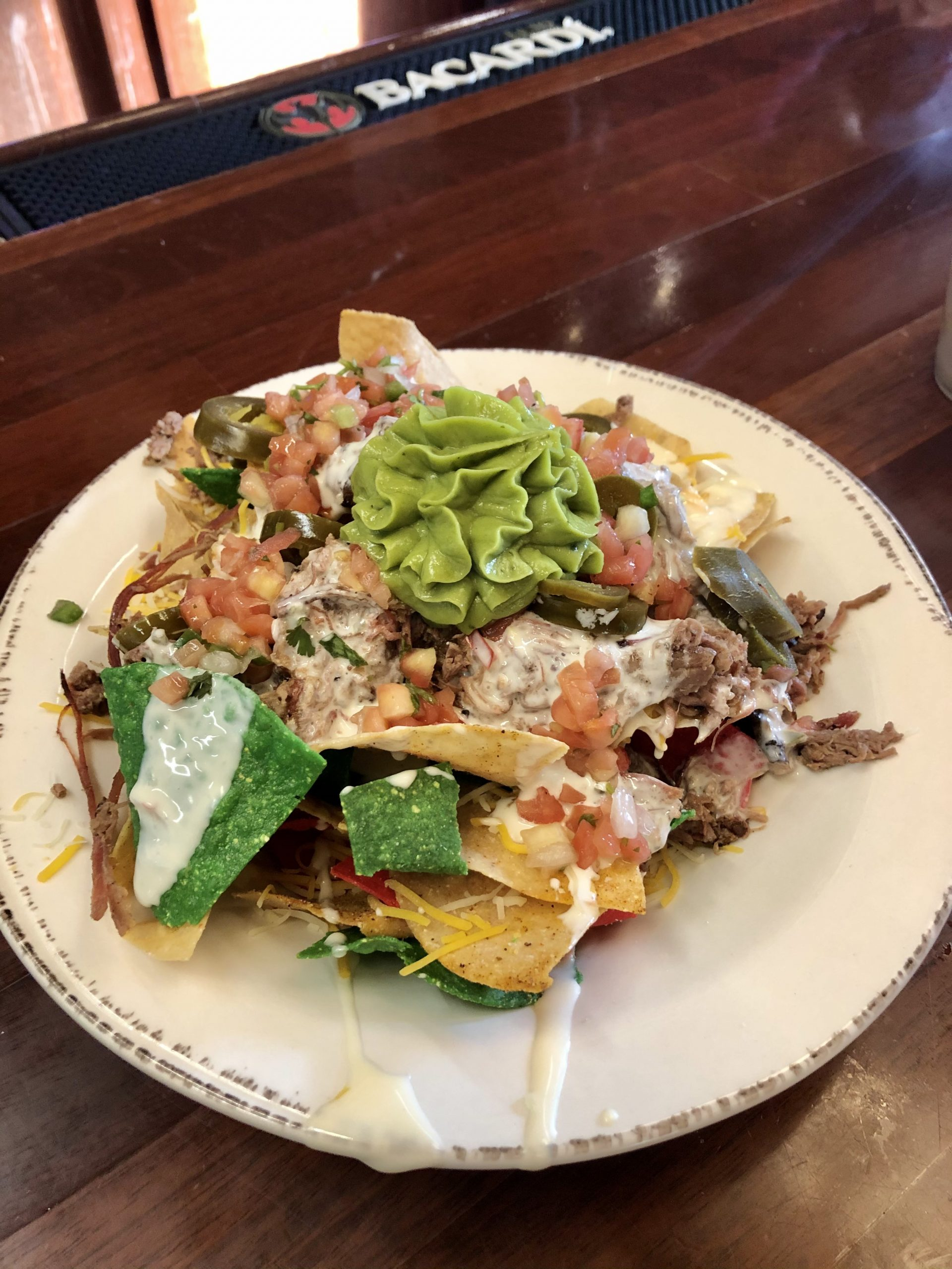 Plate of nachos with queso and lots of other yummy toppings