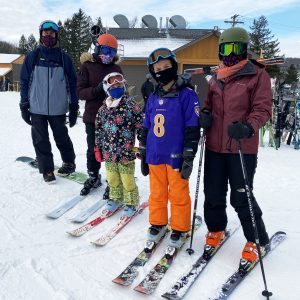 Family of 5 standing together in the snow with their skis on, ready for some fun at Greek Peak Mountain