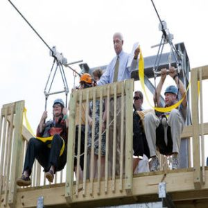 two people getting ready to zip line, from the starting point. There is a man standing behind them getting them set up.
