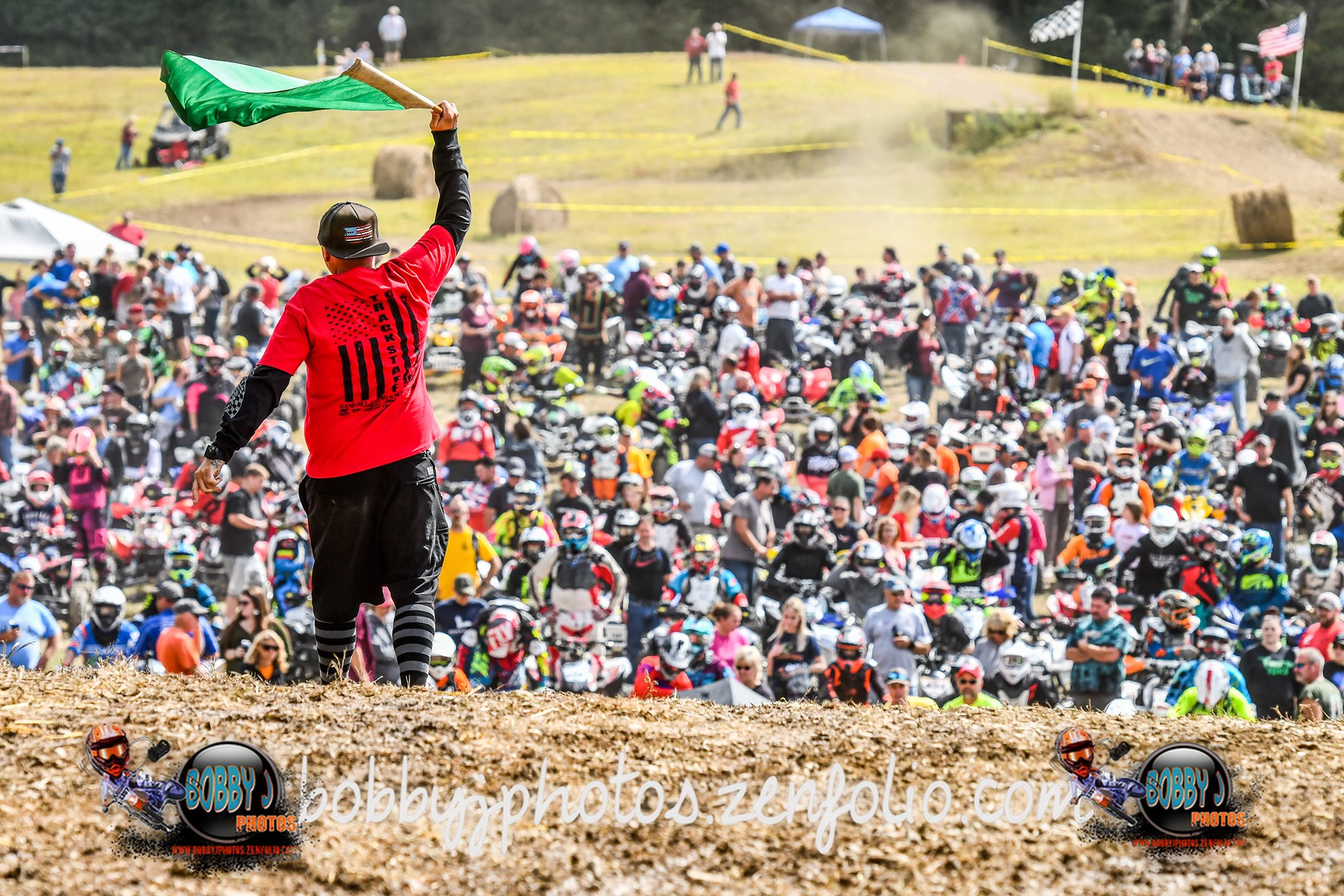 picture of another harescramble event put on by Mark Potter and his crew. Picture shows Mark waving a flag in front of a large crowd of people on a race track.